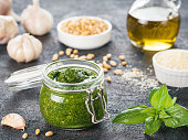 Homemade pesto sauce and ingredients on dark cement background. Close up wiev of basil pesto in glass jar with ingredients.