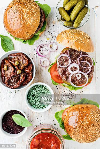 Homemade beef burgers with onion, pickles, fresh vegetables, spices, sun-dried tomatoes and tomato sauce on serving wooden board over white painted background