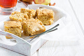 Homemade blondie (blonde) brownies apple cake, square slices in wooden tray, horizontal, copy space