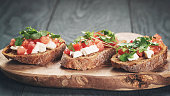 homemade bruschetta with cheese and vegetables, shallow focus