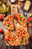 homemade bruschetta with cherry tomatoes and basil on rustic wooden table