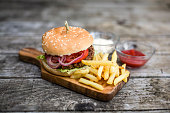 Homemade burger with lettuce, meat, tomato, onion and french fries on chopping board