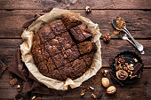 homemade chocolate brownie on dark wooden background, top view
