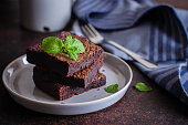 Homemade chocolate brownies on dark stone background