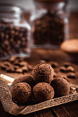 Homemade dark chocolate truffles in cocoa powder on dark brown background. Vintage still life with bonbons