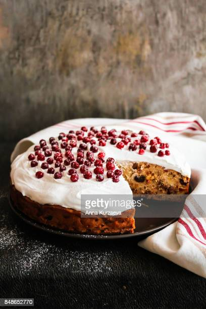 Homemade christmas cake with dried fruits decorated with sweet vanilla meringue, fresh cranberry and icing sugar on a plate, selective focus