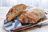 Traditional Italian bread on the kitchen table with a linen towel.