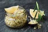 Body scrub of sea salt with lemon, rosemary and olive oil in glass jar on stone table, homemade cosmetic for Spa care