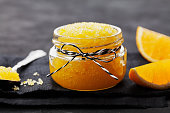 Orange body scrub with sugar and coconut oil in glass jar on black table. Homemade cosmetic for peeling and spa care