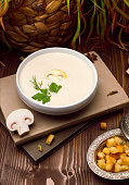 A bowl of delicious homemade cream of mushroom soup with roasted bread. - Image