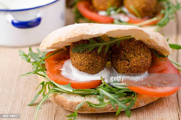 Homemade falafel, tomato, yoghurt sauce, rocket and mint in pita bread on chopping board