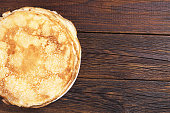 Homemade fried pancake in plate on dark wooden background, top view. Space for text