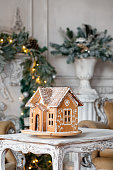 Homemade gingerbread house on background room decorated for Christmas