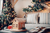 Homemade gingerbread house on light room background.