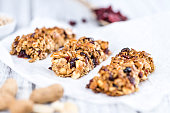 Homemade Granola Bars with Peanuts and Cranberries (selective focus) as detailed close-up shot