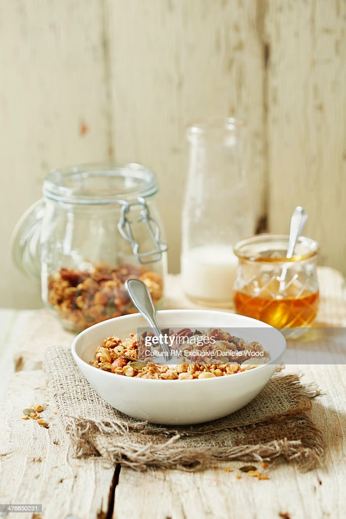 Homemade granola for breakfast with milk and honey on a light wooden background