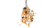 Homemade granola with honey, oatmeal, cashew nut, almond, pistachio, raisin and cranberry on white background