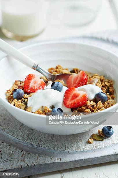 Homemade granola with natural yoghurt and strawberries and blueberries for breakfast