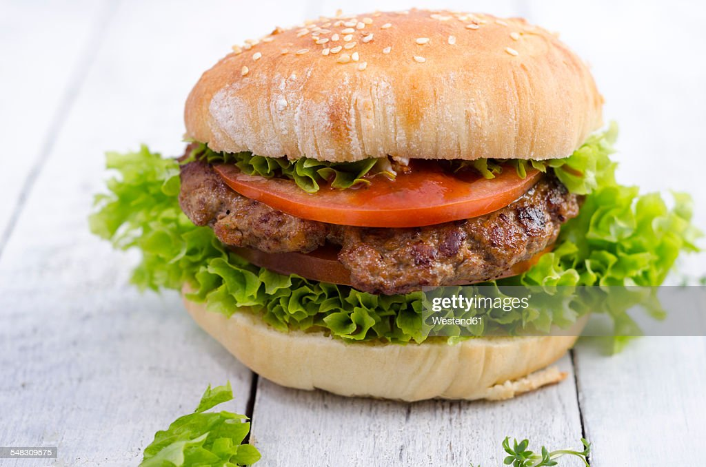 Homemade hamburger with minced beef and lettuce on sesame roll
