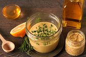 Homemade honey mustard dressing with chives on a table