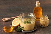 Homemade honey mustard dressing on wooden table