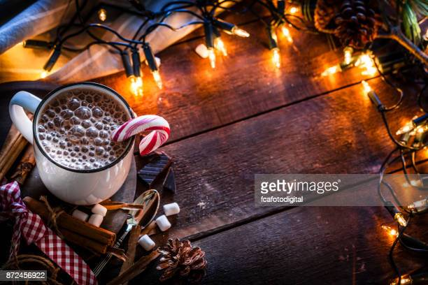 Homemade hot chocolate mug with marshmallows on rustic wooden Christmas table