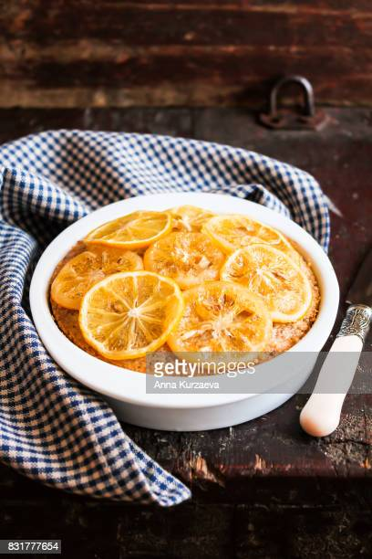 Homemade lemon cake with candied lemon sliced fruit in a bowl on a wooden table, selective focus