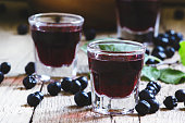 Homemade liqueur from aronia, fresh berries on a vintage wooden background, selective focus