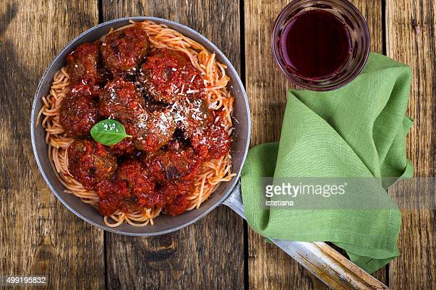 Homemade meatball with Italian pasta in frying pan on  rustic wooden table
