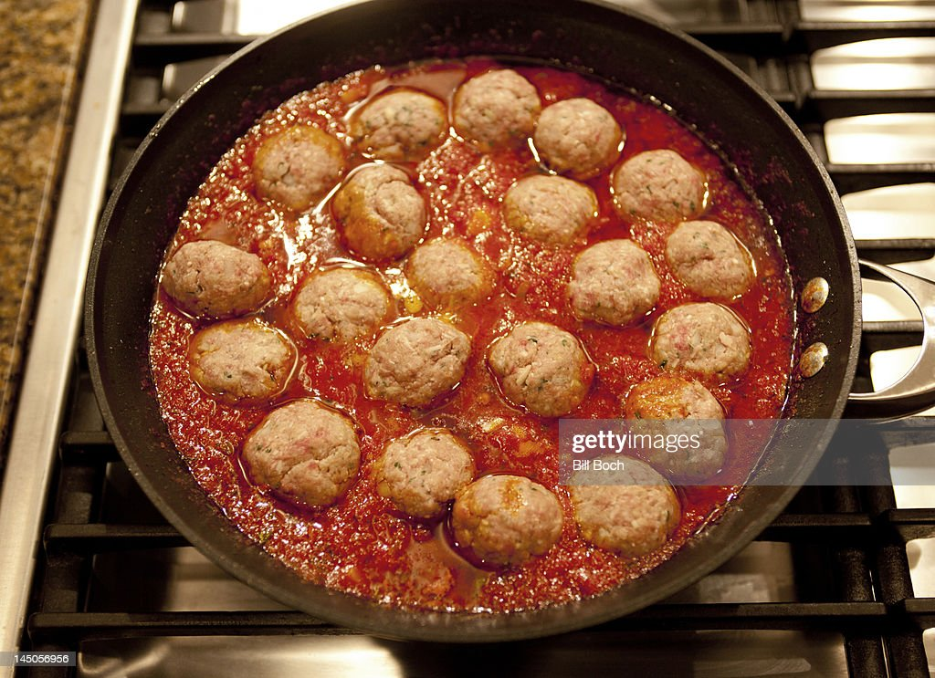 Homemade meatballs and sauce cooking on the stove : Stock Photo