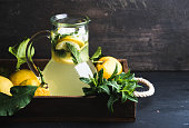 Homemade lemonade with mint and ice, served with fresh lemons in wooden tray over dark background, selective focus, copy space.