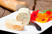 Homemade nasturtium herb butter on a plate with a piece of baguette on a rustic wooden table
