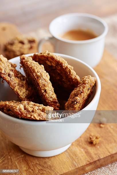 Homemade oat cookies in a bowl with a cup of coffee