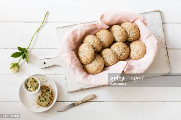 Homemade oat rolls with compound butter and a rose