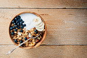 Homemade oatmeal granola with peanuts, blueberry and banana in wooden bowl, sunny morning