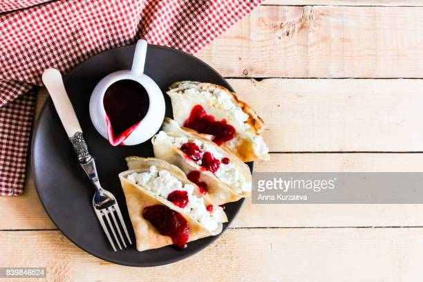 Homemade pancakes with cottage cheese and cranberry sauce on a plate, selective focus