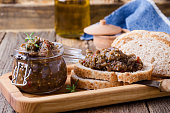 Homemade pate of eggplant. Paste in glass jar on rustic wooden table. Useful and healthy vegetarian food