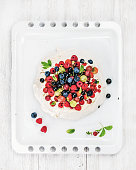 Homemade Pavlova cake with fresh garden berries on white baking tray over white painted wooden background, top view, vertical composition