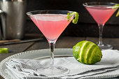 Homemade Pink Vodka Cosmopolitan Drink with a Lime Garnish