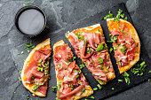 Homemade pizza with jamon serrano, paleta iberica on slate plate. Stone background