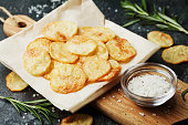 Homemade potato chips with sea salt and herb on wooden cutting board