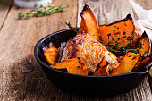 Homemade roast chicken thighs with butternut squash and thyme herb in cast iron skillet on rural wooden table
