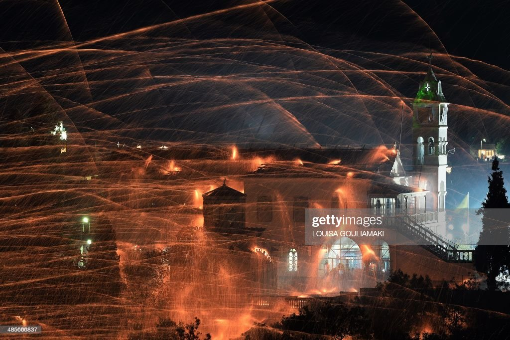 Homemade rockets streak through the sky targeting a church of Panagia Erithiani , during a traditional Easter celebration in the village of Vrontados, on the Greek island of Chios, late on April 19, 2014. As a variation of the Greek habit of throwing fireworks during the celebration of the Orthodox service at midnight before Easter Sunday, two rival church parishes in the town, the Agios Markos and Panagia Erithiani churches, perform a 'Rocket War' by firing thousands of homemade rockets towards each other while services are held.