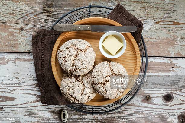 Homemade rye bread rolls on wooden plate and cooling grid
