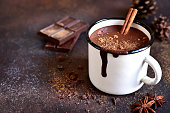Homemade spicy hot chocolate with cinnamon in enamel mug on a slate,stone or concrete background.