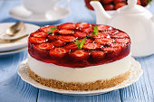 Homemade strawberry cheesecake on blue wooden background.