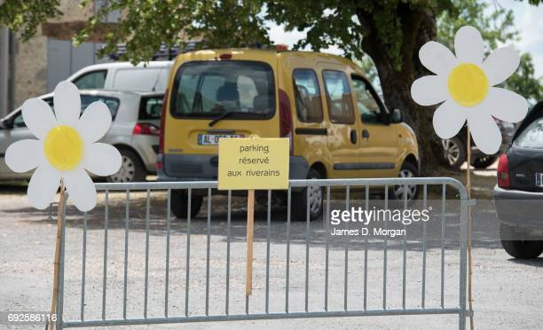 Homemade sunflowers made of cardboard and paper plates together with a no parking sign on June 5 2017 in Saussignac France Monday is a public holiday...