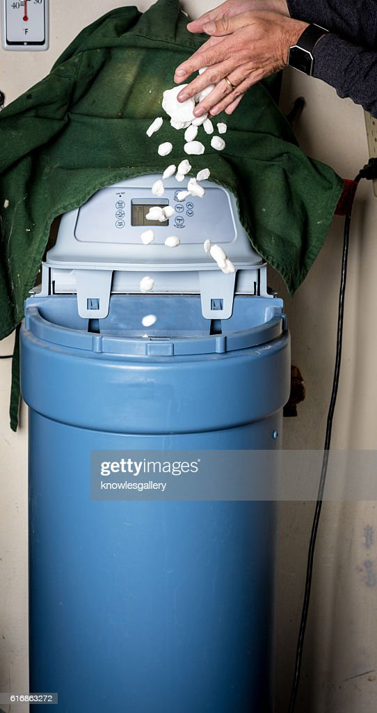 Homeowner adds salt to a water softener : Stock Photo