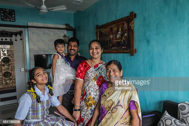 Homeowner and former slum dweller Swarangi Pingle second right stands for a photograph with her family inside her home developed by Omkar Realtors...