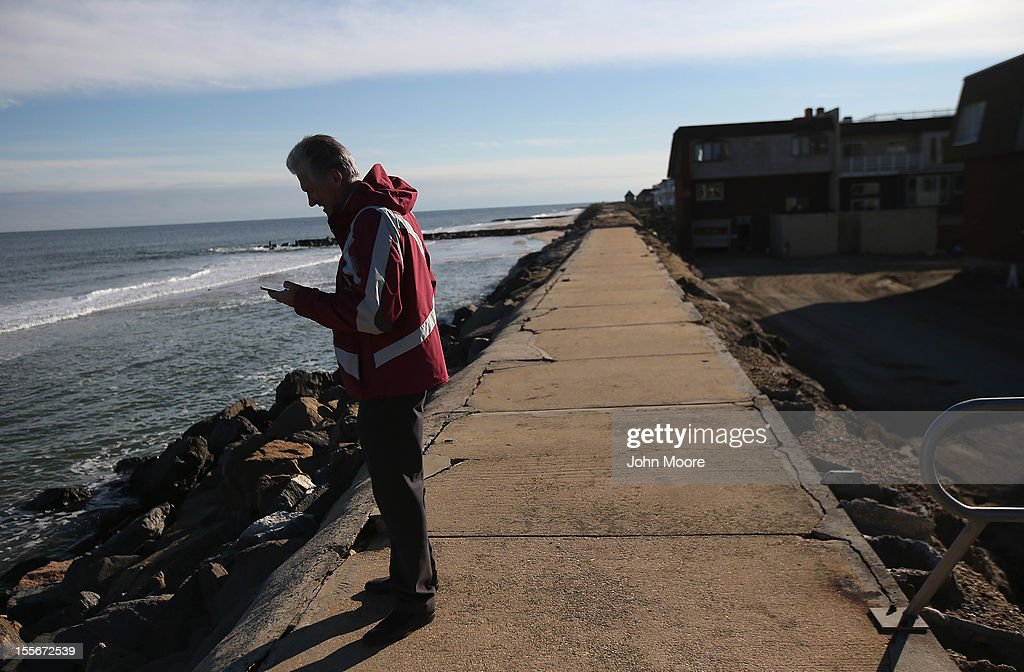 A homeowner checks cell phone signal near damaged seaside condos on November 6, 2012 in Sea Bright, New Jersey. Sea Bright was devastated by Superstorm Sandy, and officials allowed residents to come home for a day to salvage valuables from the debris.